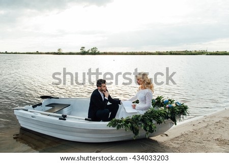 Happy young couple with a bouquet and a wreath hug sitting in a boat on the lake and sky background, lifestyle, love, relationships