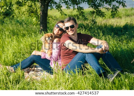 Happy young couple with a dog sitting on the grass in the park