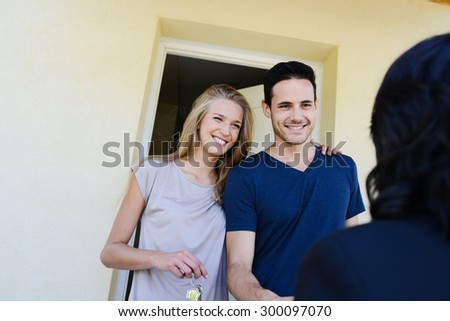 happy young couple with a real estate agent getting the keys of their new house