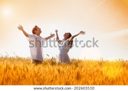 Happy, young couple with arms outstretched ,enjoying in the wheat field, summer season. Sunset light, flare light, copy space  - stock photo