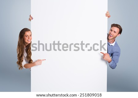 Happy young couple with blank board against grey vignette