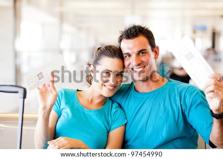 happy young couple with boarding pass at airport - stock photo