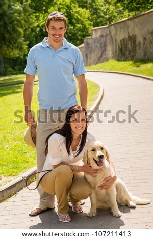 Happy  young couple with dog posing on sunny park alley