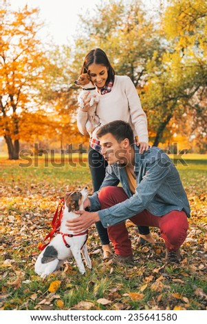 Happy young couple with dogs playing outdoors in autumn park - stock photo