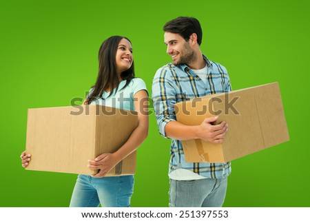 Happy young couple with moving boxes against green vignette
