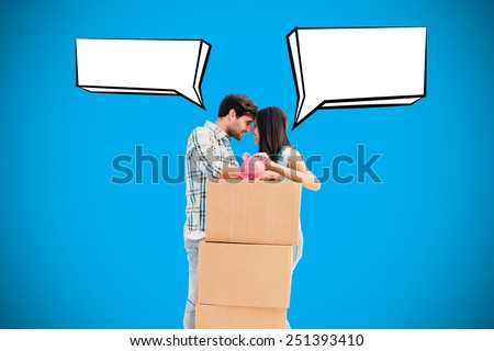 Happy young couple with moving boxes and piggy bank against blue background with vignette - stock photo