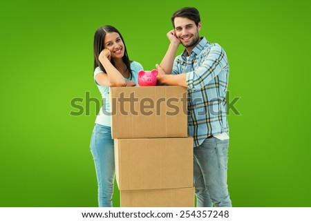Happy young couple with moving boxes and piggy bank against green vignette - stock photo