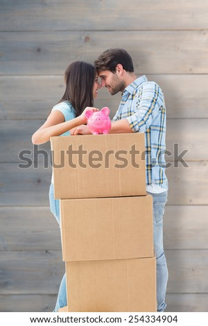 Happy young couple with moving boxes and piggy bank against pale grey wooden planks - stock photo