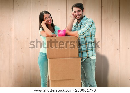 Happy young couple with moving boxes and piggy bank against wooden planks - stock photo