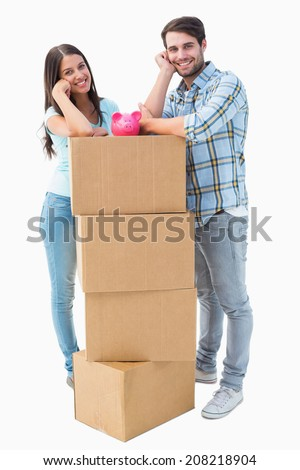 Happy young couple with moving boxes and piggy bank on white background - stock photo