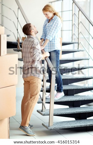 Happy young couple with moving boxes on stairs indoors