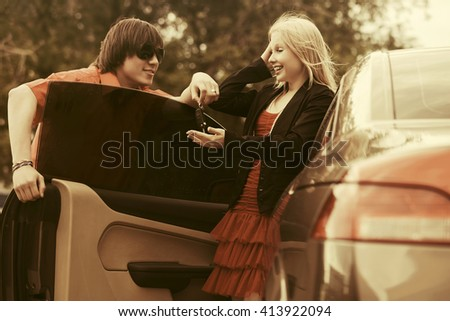Happy young couple with new convertible car - stock photo
