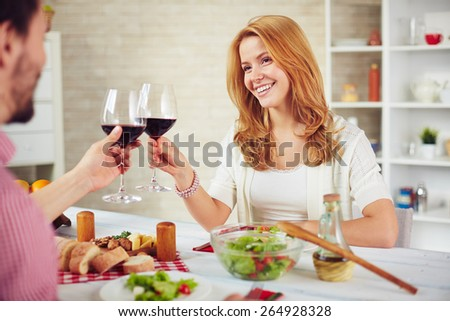 Happy young couple with red wine sitting by table and toasting