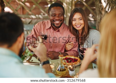 Happy young couple with red wine sitting by Thanksgiving table - stock photo