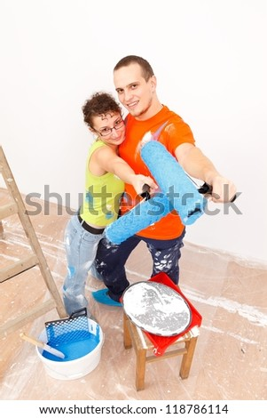 Happy young couple with roller brush near the ladder
