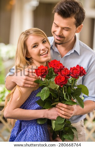 Happy young couple with roses bouquet on a date. - stock photo