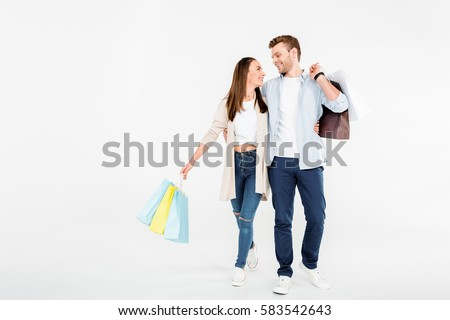 Happy young couple with shopping bags hugging and looking at each other isolated on white