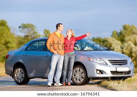 Happy young couple with their new car. Woman show something by hand. Looking at something above.
