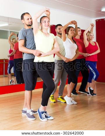 Happy young couples dancing Latino dance in class   - stock photo
