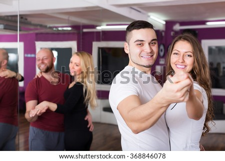 Happy young couples enjoying of partner dance and smiling - stock photo