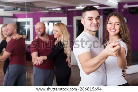 Happy young couples enjoying of partner dance and smiling indoor - stock photo