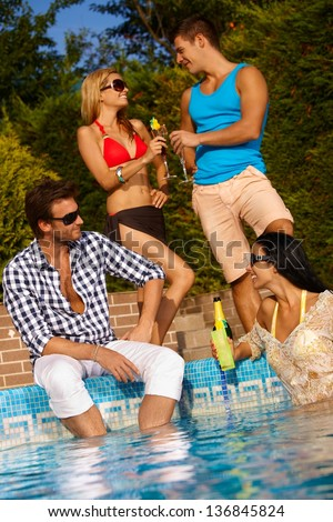 Happy young couples having fun by swimming pool. - stock photo