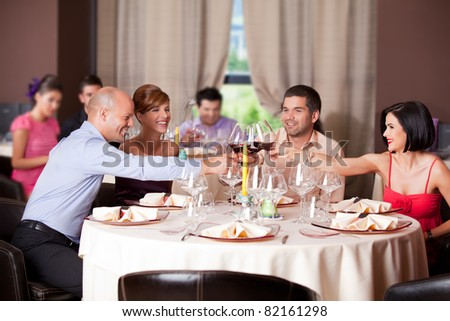 happy young couples toasting restaurant table - stock photo