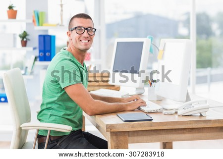 Happy young creative businessman typing on the computer - stock photo