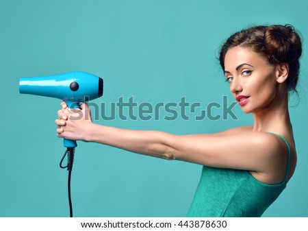 Happy young curly brunette woman with hair dryer on blue mint background. Hair style beauty concept - stock photo