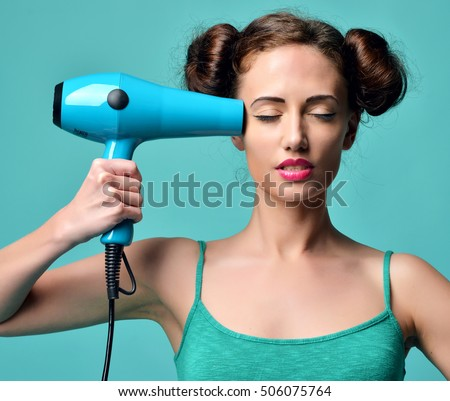 Happy young curly brunette woman with hair dryer on blue mint background. Hair style beauty concept