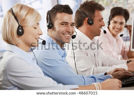 Happy young customer service operator talking via headset, typing on keyboard, looking at camera, smiling. - stock photo