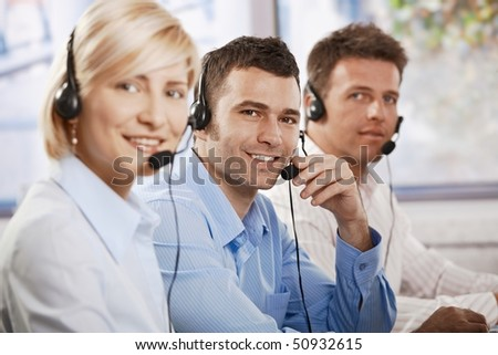 Happy young customer service operators receicving calls on headset, looking at camera, smiling. - stock photo