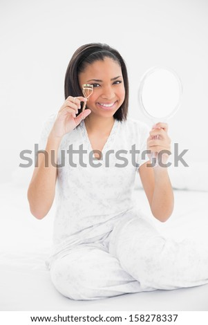 Happy young dark haired model using eyelash curler in bright bedroom