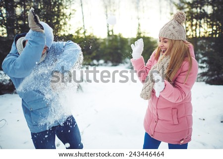 Happy young dates playing snowballs outdoors - stock photo