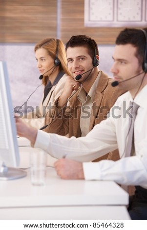 Happy young dispatcher working in callcenter, smiling.? - stock photo