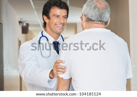 Happy young doctor assisting senior man in the hospital