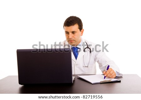 Happy young doctor working on a laptop against white background - stock photo