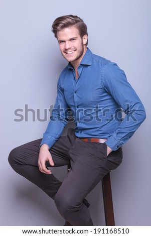 happy young elegant casual man smiling to the camera while sitting on a high chair