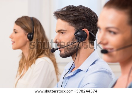 Happy young employees working in call centre. Portrait of a young attractive telephone operator working in a call center. Customer service representative wearing a headset at the office.  - stock photo