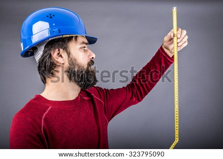 Happy young engineer with hardhat holding a measuring tape over gray background - stock photo
