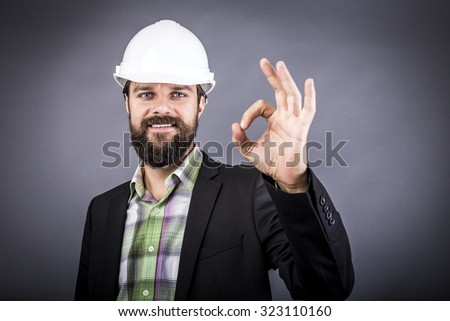 Happy young engineer with hardhat showing ok sign over gray background - stock photo