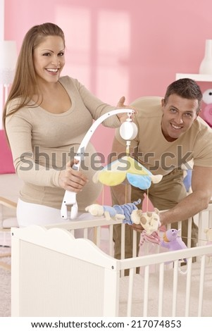 Happy young expecting couple preparing baby's room and cot.