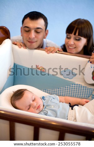 happy young family admires a sleeping newborn son - stock photo