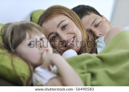 happy young family at home relaxing in bed