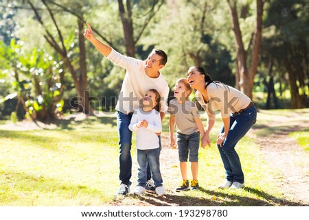 happy young family bird watching in forest - stock photo