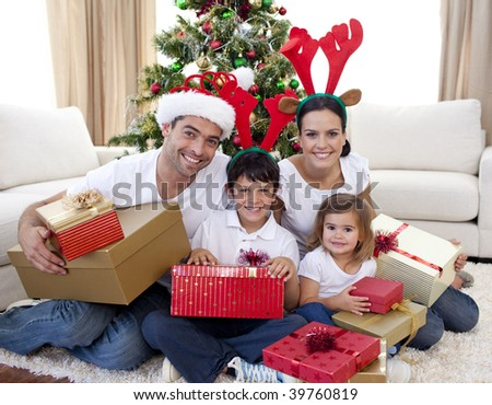 Happy young family celebrating Christmas at home - stock photo