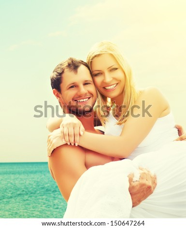 happy young family couple in love hugging and laughing on the beach at Sea - stock photo