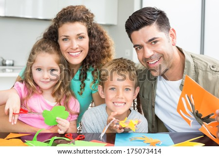 Happy young family doing arts and crafts at the table at home in kitchen - stock photo