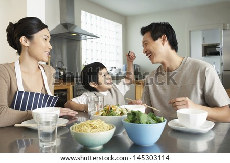 Happy young family enjoying meal at the kitchen table in house - stock photo