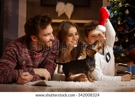 Happy young family enjoying playing with new puppy at christmas. - stock photo